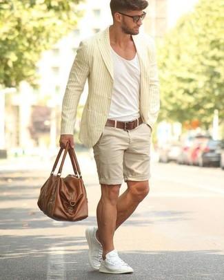 Как и с чем носить: желтый хлопковый пиджак в вертикальную полоску, белая футболка с круглым вырезом, бежевые шорты, белые низкие кеды из плотной ткани