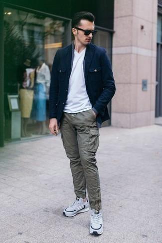 Белая футболка с v-образным вырезом: с чем носить и как сочетать мужчине: Белая футболка с v-образным вырезом и оливковые брюки карго позволят создать легкий и практичный образ для выходного в парке или вечера в пабе с друзьями. Любишь смелые сочетания? Можешь закончить свой образ бело-темно-синими кроссовками.