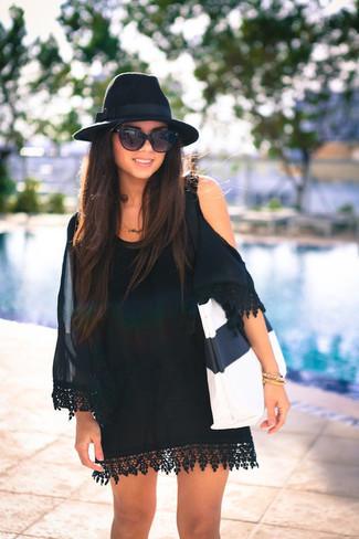 Как и с чем носить: черное шелковое платье с открытыми плечами, бело-черная кожаная большая сумка, черная шерстяная шляпа, черные солнцезащитные очки