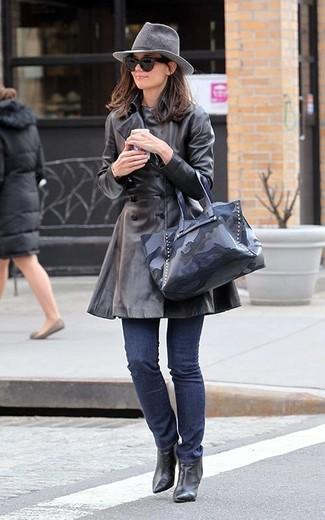 Как и с чем носить: черный кожаный плащ, темно-синие джинсы, черные кожаные ботильоны, темно-синяя кожаная большая сумка с камуфляжным принтом