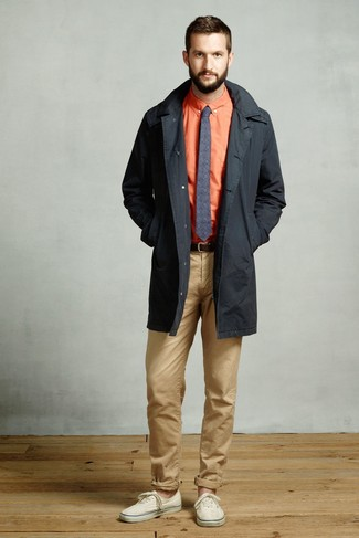 Как и с чем носить: черный плащ, оранжевая классическая рубашка, светло-коричневые брюки чинос, бежевые низкие кеды из плотной ткани