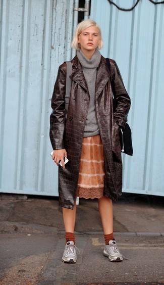 Как и с чем носить: темно-коричневый кожаный плащ, серый свитер с хомутом, оранжевое платье-комбинация c принтом тай-дай, серебряные кроссовки