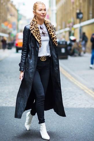 Как и с чем носить: черный кожаный плащ, серая футболка с круглым вырезом с принтом, черные джинсы скинни, белые ботильоны на резинке