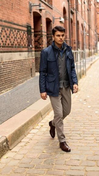 С чем носить коричневые брюки чинос: Дуэт темно-синей полевой куртки и коричневых брюк чинос вдохновляет на проявление личного стиля. Дополнив ансамбль темно-коричневыми кожаными оксфордами, получим потрясающий результат.