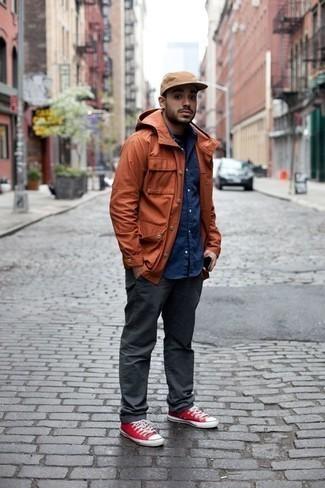 Красные низкие кеды из плотной ткани: с чем носить и как сочетать мужчине: Оранжевая полевая куртка и темно-серые брюки чинос надежно закрепились в гардеробе многих мужчин, помогая составлять незаезженные и практичные луки. В сочетании с красными низкими кедами из плотной ткани весь лук выглядит очень динамично.