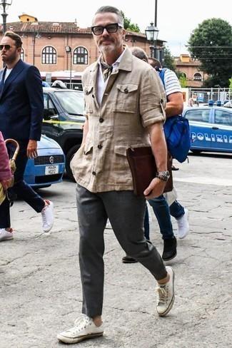 Темно-серые брюки чинос: с чем носить и как сочетать: Поклонникам повседневного стиля придется по душе сочетание бежевой льняной полевой куртки и темно-серых брюк чинос. Что касается обуви, можешь отдать предпочтение комфорту и выбрать белые низкие кеды из плотной ткани.