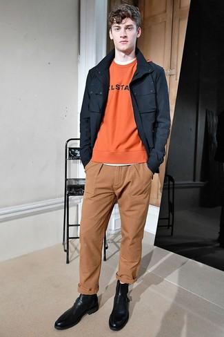 Как и с чем носить: черная полевая куртка, оранжевый свитшот с принтом, белая футболка с круглым вырезом, светло-коричневые брюки чинос