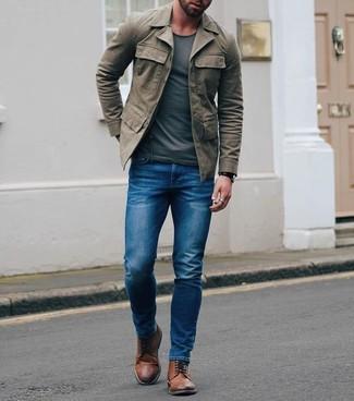 Как и с чем носить: оливковая полевая куртка, темно-серая футболка с круглым вырезом, синие зауженные джинсы, коричневые кожаные ботинки броги