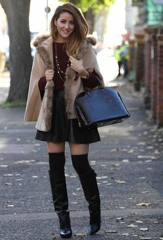 Как и с чем носить: бежевое пончо, темно-красный свитер с круглым вырезом, черная кожаная короткая юбка-солнце, черные кожаные сапоги