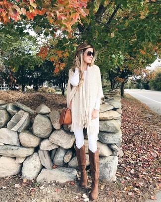 Коричневые замшевые сапоги: с чем носить и как сочетать: Бежевое вязаное пончо и белые джинсы скинни великолепно подходят для создания городского образа как для будничных, так и для выходных дней. Не прочь сделать наряд немного элегантнее? Тогда в качестве обуви к этому ансамблю, стоит выбрать коричневые замшевые сапоги.
