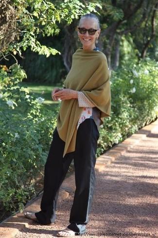 Как и с чем носить: оливковое пончо, белая футболка с длинным рукавом с принтом, черные широкие брюки, бежевые кожаные сандалии на плоской подошве