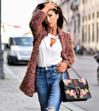 Как и с чем носить: пурпурное пальто букле, белая блузка с длинным рукавом, синие рваные джинсы, черная кожаная сумка-саквояж с цветочным принтом