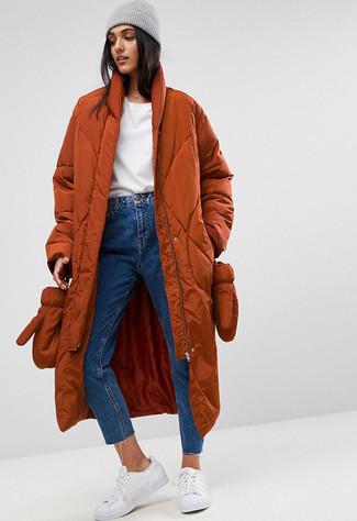 Как и с чем носить: табачный пуховик, белый свитер с круглым вырезом, синие джинсы, белые кожаные низкие кеды