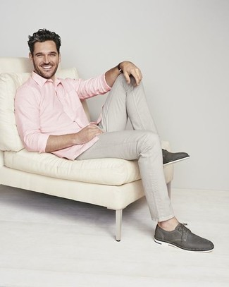 С чем носить серые брюки чинос: Образ из розовой рубашки с длинным рукавом и серых брюк чинос позволит создать необыденный мужской лук в стиле кэжуал. Темно-серые кожаные туфли дерби добавят луку эффектности.
