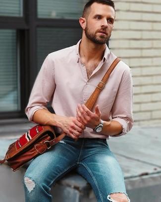 Как и с чем носить: розовая льняная рубашка с длинным рукавом, синие рваные зауженные джинсы, коричневая кожаная сумка почтальона, серебряные часы