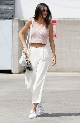 Как Kendall Jenner носит Розовый укороченный топ, Белые широкие брюки, Белые низкие кеды, Белая кожаная сумка через плечо