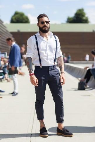 """Сочетание белой рубашки с длинным рукавом и темно-синих брюк чинос позволит создать ощущение """"элегантной свободы"""". Сделать образ изысканнее помогут черные замшевые лоферы с кисточками."""