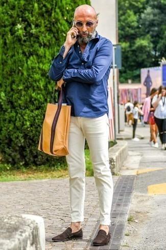 Темно-коричневые замшевые лоферы: с чем носить и как сочетать мужчине: Комбо из темно-синей рубашки с длинным рукавом из шамбре и белых брюк чинос поможет подчеркнуть твой индивидуальный стиль и выигрышно выделиться из серой массы. Хочешь добавить в этот лук нотку классики? Тогда в качестве обуви к этому ансамблю, обрати внимание на темно-коричневые замшевые лоферы.