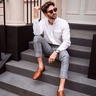 С чем носить темно-коричневые солнцезащитные очки мужчине: Если ты ценишь комфорт и практичность, белая рубашка с длинным рукавом и темно-коричневые солнцезащитные очки — отличный выбор для привлекательного повседневного мужского образа. Такой образ получает новое прочтение в паре с табачными кожаными лоферами.