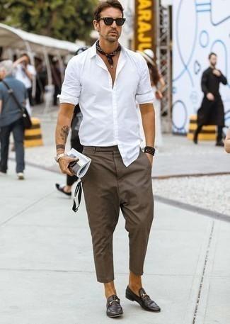 С чем носить черные солнцезащитные очки мужчине: Если у тебя планируется насыщенный день, сочетание белой рубашки с длинным рукавом и черных солнцезащитных очков поможет создать удобный лук в расслабленном стиле. Завершив лук темно-коричневыми кожаными лоферами, можно получить потрясающий результат.