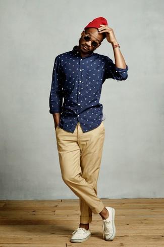 Как и с чем носить: темно-синяя рубашка с длинным рукавом с принтом, светло-коричневые брюки чинос, белые низкие кеды из плотной ткани, красная шапка