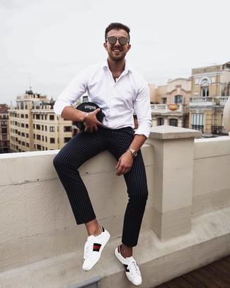 Как и с чем носить: белая рубашка с длинным рукавом, черные брюки чинос в вертикальную полоску, белые кожаные низкие кеды с принтом, коричневые солнцезащитные очки