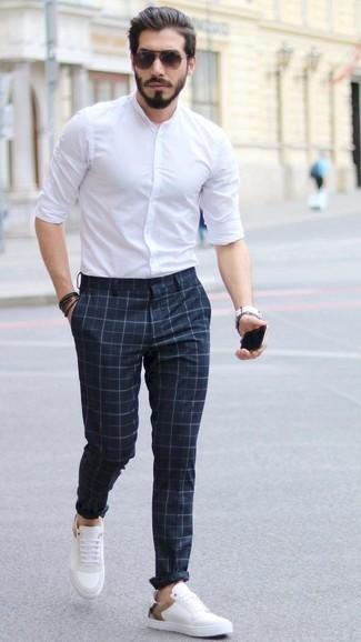 Модные мужские луки 2020 фото в теплую погоду: Белая рубашка с длинным рукавом и темно-синие брюки чинос в клетку идеально подходят для создания городского лука как для будничных, так и для выходных дней. Белые кожаные низкие кеды чудесно впишутся в образ.