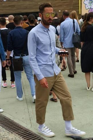 Светло-коричневые брюки чинос: с чем носить и как сочетать: Голубая рубашка с длинным рукавом в сочетании со светло-коричневыми брюками чинос продолжает нравиться молодым людям, которые любят одеваться со вкусом. Любители рискованных сочетаний могут закончить лук белыми кожаными низкими кедами.