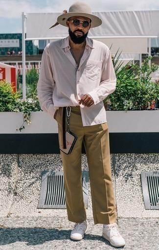 Розовая рубашка с длинным рукавом: с чем носить и как сочетать мужчине: Несмотря на свою простоту, тандем розовой рубашки с длинным рукавом и светло-коричневых брюк чинос неизменно нравится стильным молодым людям, неизбежно покоряя при этом дамские сердца. Любишь экспериментировать? Дополни лук белыми кожаными низкими кедами.