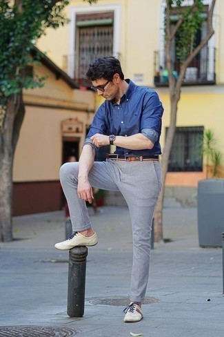 Коричневые солнцезащитные очки: с чем носить и как сочетать мужчине: Такое простое и комфортное сочетание вещей, как синяя рубашка с длинным рукавом из шамбре и коричневые солнцезащитные очки, полюбится молодым людям, которые любят проводить дни активно. Не прочь сделать ансамбль немного элегантнее? Тогда в качестве обуви к этому луку, обрати внимание на бежевые кожаные низкие кеды.