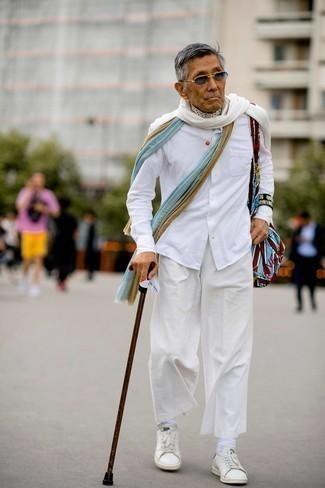 Как одеваться мужчине за 60: Белая рубашка с длинным рукавом и белые брюки чинос помогут создать нескучный и стильный образ. Почему бы не привнести в этот ансамбль чуточку беззаботства с помощью белых кожаных низких кед?