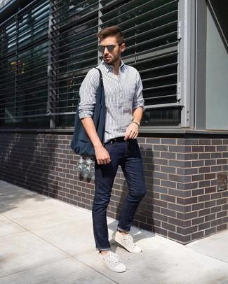 Как и с чем носить: бело-темно-синяя льняная рубашка с длинным рукавом в вертикальную полоску, темно-синие джинсы, бежевые низкие кеды из плотной ткани, темно-синяя большая сумка из плотной ткани