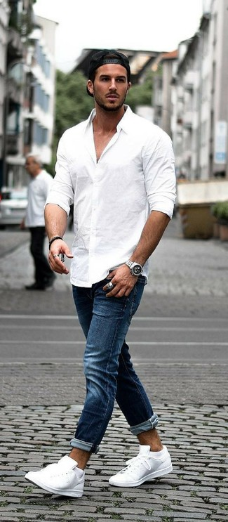 Как и с чем носить: белая рубашка с длинным рукавом, темно-синие джинсы, белые кожаные низкие кеды, черная бейсболка