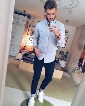 Темно-синие зауженные джинсы: с чем носить и как сочетать мужчине: Практичное сочетание голубой рубашки с длинным рукавом и темно-синих зауженных джинсов вне всякого сомнения будет обращать на себя взгляды прекрасных дам. Пара белых кожаных низких кед чудесно гармонирует с остальными элементами лука.