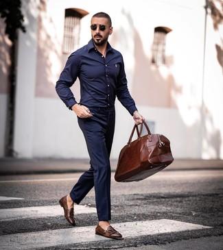 Коричневая кожаная дорожная сумка: с чем носить и как сочетать мужчине: Темно-синяя рубашка с длинным рукавом и коричневая кожаная дорожная сумка — отличный выбор для веселого выходного дня. Теперь почему бы не привнести в этот ансамбль на каждый день чуточку утонченности с помощью коричневых кожаных монок с двумя ремешками?
