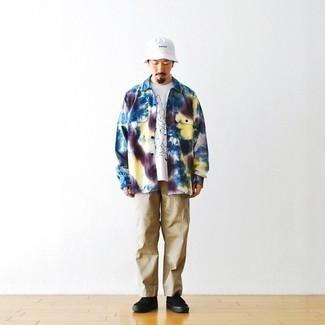 Как одеваться мужчине за 60: Разноцветная рубашка с длинным рукавом с принтом тай-дай и светло-коричневые брюки чинос — неотъемлемые составляющие в гардеробе мужчин с хорошим чувством стиля. В паре с этим ансамблем наиболее гармонично смотрятся черные низкие кеды из плотной ткани.