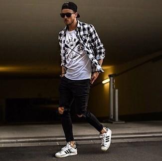 Как и с чем носить: черно-белая рубашка с длинным рукавом в мелкую клетку, бело-черная футболка с круглым вырезом с принтом, черные рваные зауженные джинсы, бело-черные кожаные низкие кеды в горизонтальную полоску