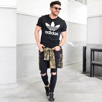 Как и с чем носить: оливковая рубашка с длинным рукавом с камуфляжным принтом, черно-белая футболка с круглым вырезом с принтом, черные рваные зауженные джинсы, черные кожаные низкие кеды