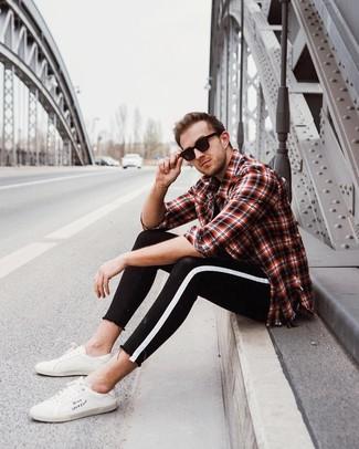 Как и с чем носить: красно-черная рубашка с длинным рукавом в шотландскую клетку, черная футболка с круглым вырезом, черно-белые зауженные джинсы, белые кожаные низкие кеды