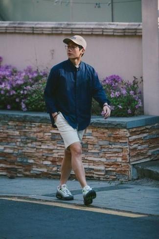 Модные мужские луки 2020 фото: Темно-синяя рубашка с длинным рукавом и белые шорты — беспроигрышный лук, если ты хочешь составить непринужденный, но в то же время модный мужской лук. Такой лук несложно адаптировать к повседневным делам, если надеть в паре с ним разноцветные кроссовки.