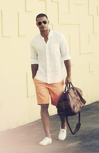 Как и с чем носить: белая рубашка с длинным рукавом, оранжевые шорты с принтом, белые слипоны, темно-коричневая кожаная дорожная сумка