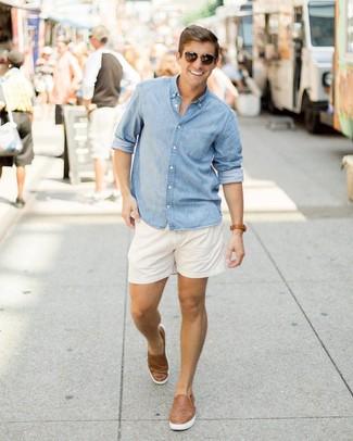 Как и с чем носить: голубая рубашка с длинным рукавом из шамбре, белые шорты, коричневые кожаные плетеные слипоны, темно-коричневые солнцезащитные очки