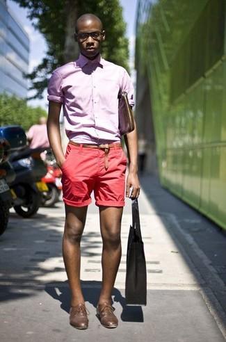 Как и с чем носить: розовая рубашка с длинным рукавом, красные шорты, коричневые кожаные туфли дерби, коричневая кожаная сумка почтальона
