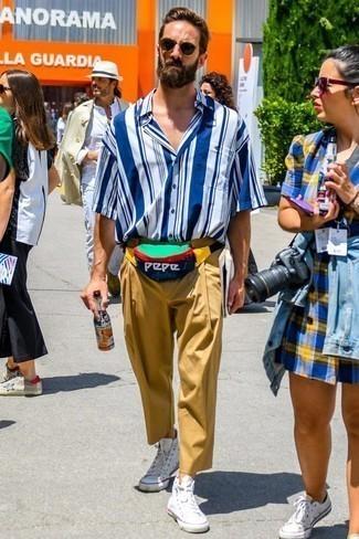 Светло-коричневые брюки чинос: с чем носить и как сочетать: Бело-синяя рубашка с коротким рукавом в вертикальную полоску и светло-коричневые брюки чинос — необходимые вещи в гардеробе любителей непринужденного стиля. Этот лук гармонично дополнят белые высокие кеды из плотной ткани.