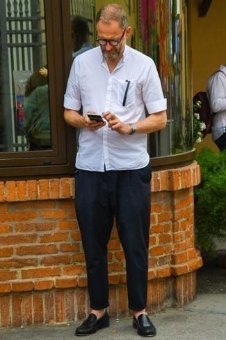 С чем носить черные кожаные лоферы мужчине: Любителям стиля кэжуал понравится лук из белой рубашки с коротким рукавом и темно-синих брюк чинос. Этот ансамбль обретет новое прочтение в паре с черными кожаными лоферами.