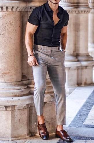 Серые брюки чинос в клетку: с чем носить и как сочетать: Темно-синяя рубашка с коротким рукавом и серые брюки чинос в клетку надежно закрепились в гардеробе современных парней, позволяя создавать незаезженные и стильные образы. Не прочь добавить в этот образ немного строгости? Тогда в качестве обуви к этому луку, выбери коричневые кожаные монки.