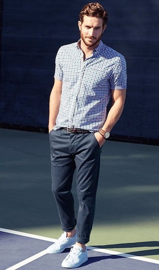 Темно-сине-белая рубашка с коротким рукавом в мелкую клетку отлично сочетается с темно-синими брюками чинос. Очень выигрышно здесь будут смотреться белые низкие кеды.