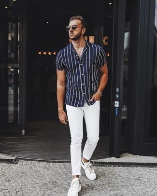Как и с чем носить: темно-сине-белая рубашка с коротким рукавом в вертикальную полоску, белые брюки чинос, белые кожаные низкие кеды, черные солнцезащитные очки