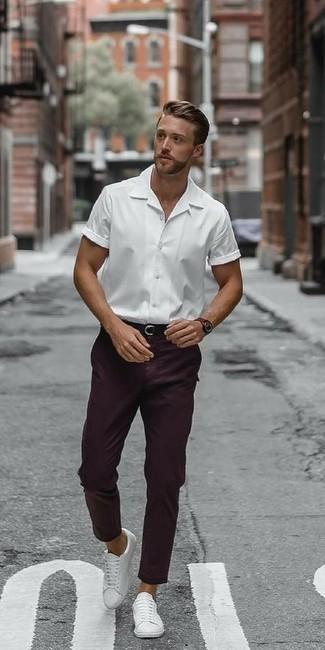С чем носить темно-пурпурные брюки чинос: Белая рубашка с коротким рукавом и темно-пурпурные брюки чинос — великолепный выбор, если ты хочешь создать лёгкий, но в то же время модный мужской образ. Весьма кстати здесь смотрятся белые кожаные низкие кеды.