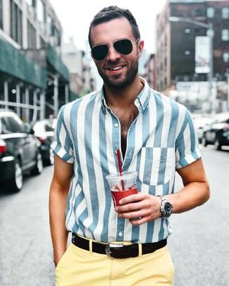 Как и с чем носить: бело-синяя рубашка с коротким рукавом в вертикальную полоску, желтые брюки чинос, черный кожаный ремень, черные солнцезащитные очки